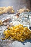 Pastaägg i mjöl och en kavel på en wood tabell Royaltyfri Fotografi