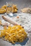 Pastaägg i mjöl och en kavel på en wood tabell Royaltyfria Bilder