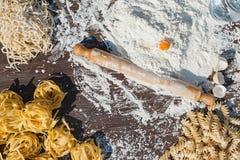 Pastaägg i mjöl och en kavel på en wood tabell Royaltyfri Foto