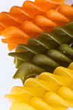 Pasta. Macro of colored raw fusilli or rotini pasta stock images