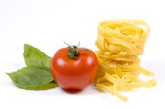 Pasta. Tagliatelle and a tomato and some basil leaves royalty free stock photos