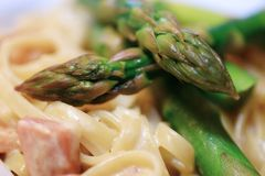 Pasta. A white plate with delicious pasta, asparagus and ham stock photo