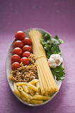 Pasta. Raw pasta with tomato, parsley and garlic close up Stock Images