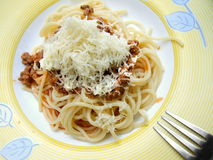 Pasta. With tomato sauce and grated cheese on top on a plate. End of fork visible royalty free stock images
