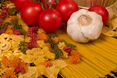 Pasta. Varieties of pasta, tomatoes and garlic closeup Royalty Free Stock Image