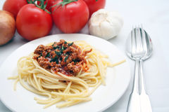 Pasta. A plate of pasta and sauce with tomatoes and garlic in the background royalty free stock photo