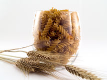 Pasta. Glass of integral, whole grain pasta, with wheat, on white background Stock Images