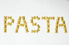 Pasta. Word written with farfalle  on white background Stock Photo