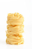 Pasta. Pile of uncooked fettuccinne isolated Royalty Free Stock Photography