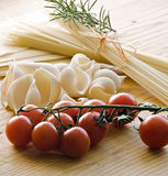 Pasta. Some kind of pasta and tomatoes at the desk Royalty Free Stock Photos