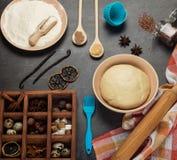 Pasta acabada en cuenco, harina, especias, huevos y herramientas, en superficie de trabajo foto de archivo