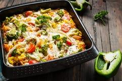Pasta al forno con i broccoli e la salsa al pomodoro kitsch su fondo di legno Immagine Stock