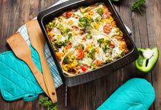 Pasta al forno con i broccoli e la salsa al pomodoro kitsch su fondo di legno Fotografia Stock