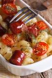Pasta al forno con i pomodori ciliegia e la salsiccia ed il primo piano della forcella Immagine Stock