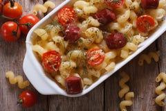 Pasta al forno con la vista superiore dei pomodori, delle salsiccie e degli ingredienti Fotografie Stock Libere da Diritti