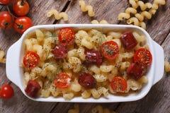 Pasta al forno con la vista superiore delle salsiccie e dei pomodori ciliegia Immagini Stock