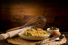 Pasta alla carbonara. Delicious spaghetti with bacon and egg called alla carbonara on wooden table Stock Images