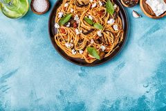 Pasta alla Norma - traditional Italian food. With eggplant, tomato, cheese and basil, top view stock images