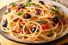 Pasta Alla Puttanesca with anchovies and black olives macro. horizontal. Pasta Alla Puttanesca with anchovies and black olives macro on a plate. horizontal stock photos