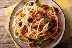 Pasta Alla Puttanesca with anchovies and black olives. horizontal top view. Pasta Alla Puttanesca with anchovies and black olives on a plate. horizontal top view royalty free stock photography
