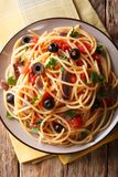 Pasta Alla Puttanesca with anchovies and black olives. Vertical. Pasta Alla Puttanesca with anchovies and black olives on a plate. Vertical top view from above royalty free stock photos