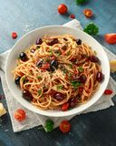 Pasta Alla Puttanesca with garlic, olives, capers, tomato and anchois fish.  stock photos