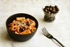 Pasta alla puttanesca. Italian home made sedani alla puttanesca Olives and tomato sauce stock photography