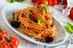 Spaghetti with tomato sauce olives and capers stock image