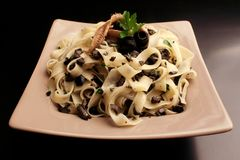 Pasta with anchovies and black olives stock photo