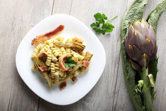 Pasta with artichoke cream and bacon. On complex background Royalty Free Stock Photography