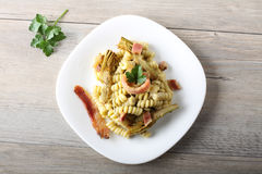 Pasta with artichoke cream and bacon. On complex background Royalty Free Stock Images