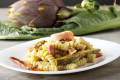 Pasta with artichoke cream and bacon. On complex background Stock Photo