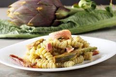Pasta with artichoke cream and bacon Stock Photo