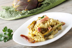 Pasta with artichoke cream and bacon. On complex background Royalty Free Stock Photo