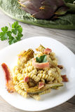 Pasta with artichoke cream and bacon. On complex background Stock Photography