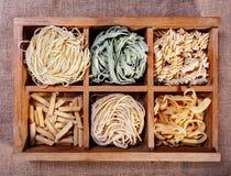 Pasta assortita nel catalogo della scatola di legno sul fondo scuro del tessuto - Immagine Stock Libera da Diritti