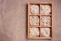 Pasta assortita nel catalogo della scatola di legno sul fondo scuro del tessuto Fotografia Stock Libera da Diritti