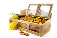 Pasta assortment. In old wooden cupboard isolated over white Stock Photo