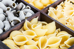 Pasta assortment background. Pasta in a wooden box. Italian pasta of different colors Royalty Free Stock Images