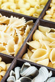 Pasta assortment background. Pasta in a wooden box. Italian pasta of different colors. focus on the paste in the middle of the frame Stock Images