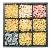 Pasta assortment background on white background. Pasta in a wooden box. Italian pasta of different colors Royalty Free Stock Photography