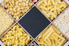 Pasta assortment and blackboard for text. Italian pasta assortment and blackboard for text Royalty Free Stock Image