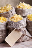 Pasta assortment in burlap bags. With pasta label for copy space Stock Images