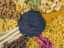Pasta assortment frame. Photo of twelve different pasta types arranged on a slate surface as a frame Royalty Free Stock Photos