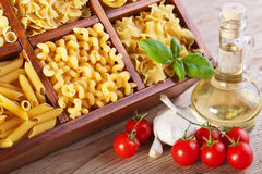 Pasta assortment and seasoning ingredients. Pasta assortment and fresh seasoning ingredients on old wooden table Stock Image