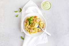 Pasta with avocado and bacon on a white background royalty free stock photography