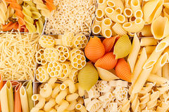 Pasta background assortment of different kinds italian macaroni in chess cells top view. Healthy traditional food backdrop Stock Photos
