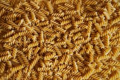 Pasta background - helix on a wooden surface. Edible texture stock photo