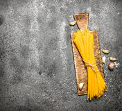 Pasta background. Spaghetti on the old Board with the garlic. Royalty Free Stock Photo