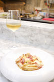 Pasta with bacon in cream sauce serving with white wine Royalty Free Stock Photo